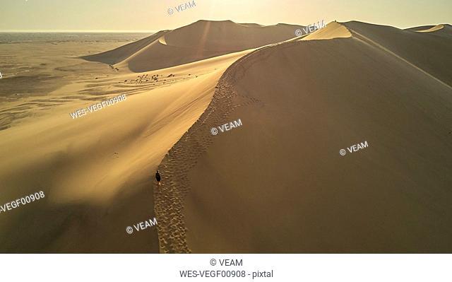 Woman in dune landscape, Namib Desert, Namibia