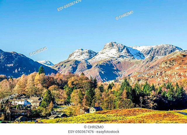 The Langdale Pikes over the village of Elterwater, Langdale, English Lake District, UK on sunny day with blue skies