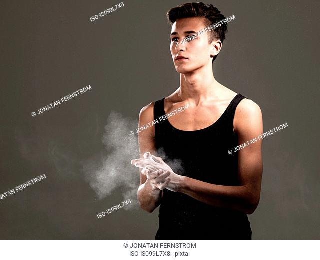 Young athlete rubbing powder on hands against grey background
