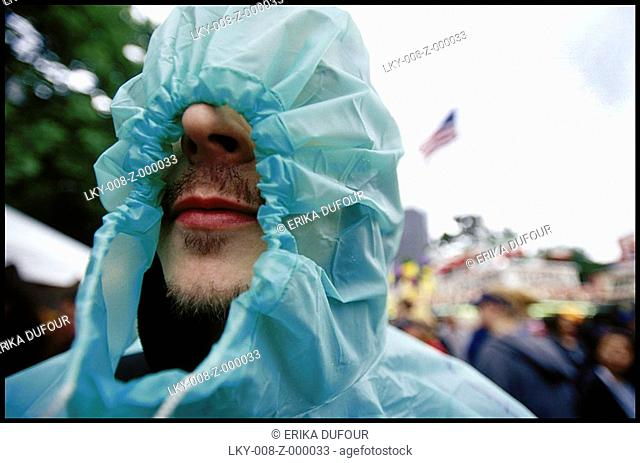 Man with poncho draws hood around nose and mouth