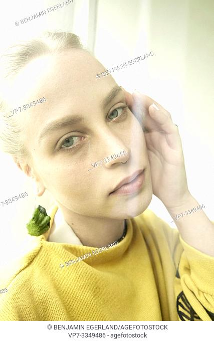 young numb woman wearing earring made of raw zucchini
