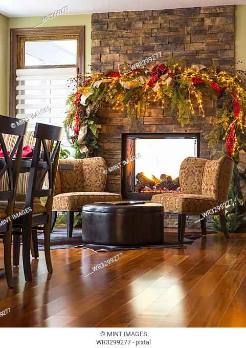 Armchairs and fireplace in living room at Christmas