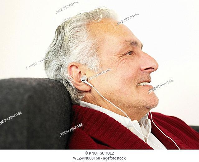Germany, Munich, Senior man listening to music, smiling
