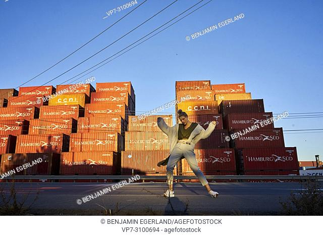 Australia, Adelaide, women's fashion blogger and actress Sarah Jeavons dancing in front ship containers