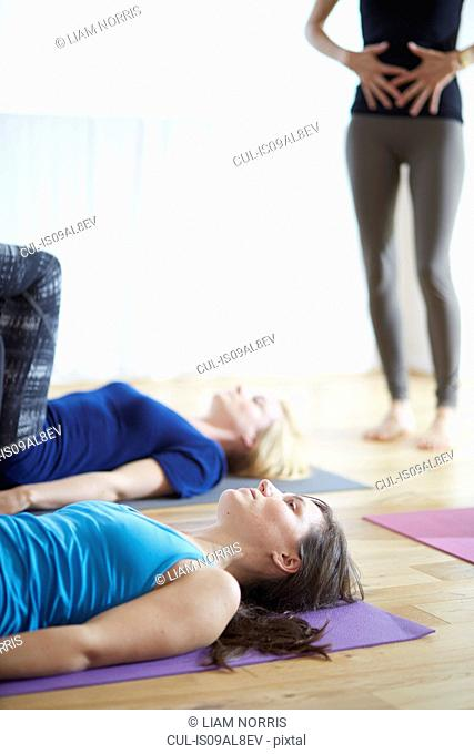 Female teacher with hands on stomach in pilates class