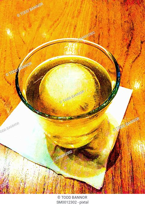 Bourbon on the rocks. Single ball of ice