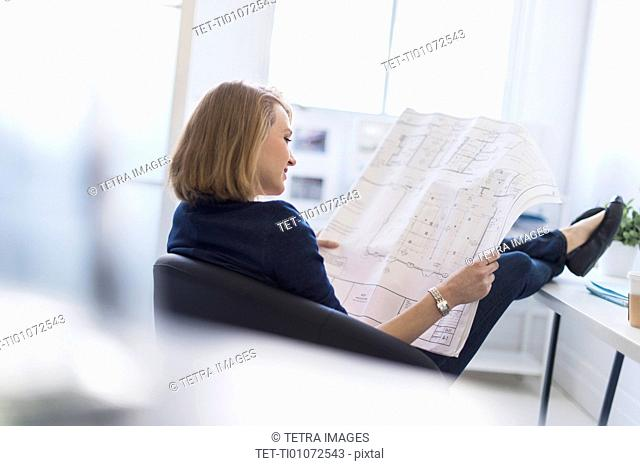 Business woman looking at blueprint in office