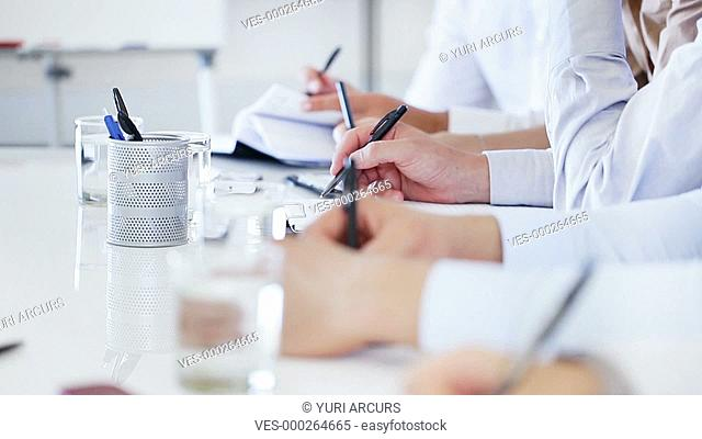 Closeup of a row of businesspeople writing at a desk