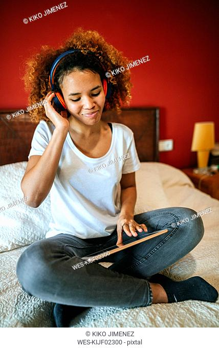 Young woman listening to music with tablet sitting on bed