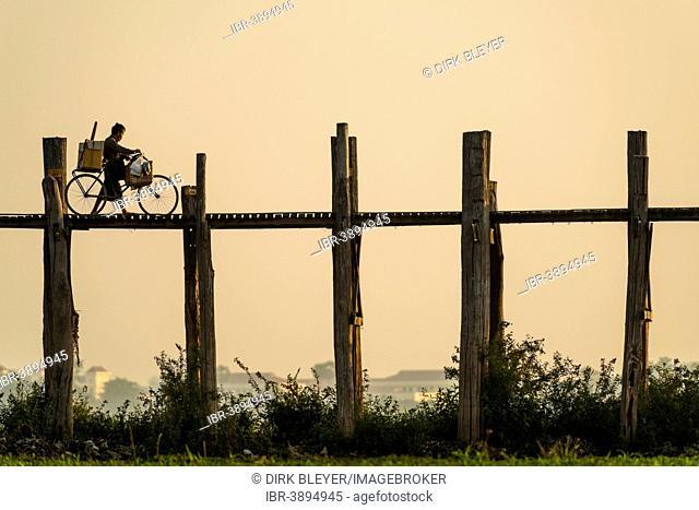 Man with a bike walking on a teak bridge, U Bein Bridge across Thaungthaman Lake in the evening light, Amarapura, Mandalay Division, Myanmar