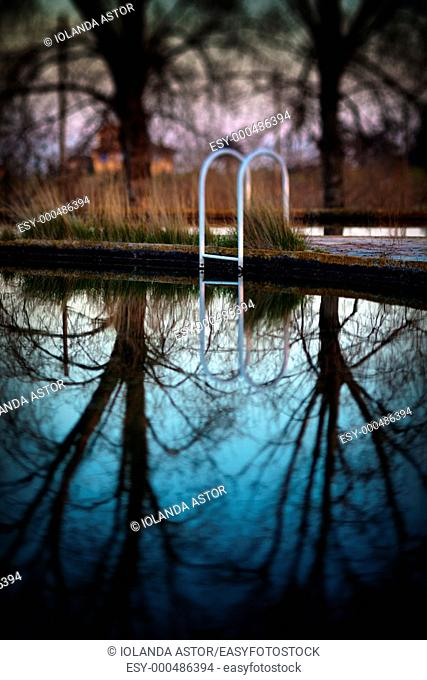 Detail of a swimming pool in one abandoned place  Reflections in the water