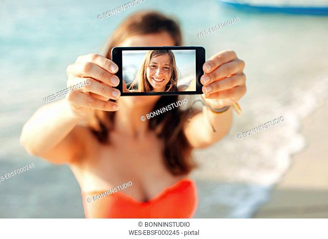 Indonesia, Gili Islands, woman on the beach showing smartphone with her selfie