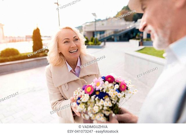 An elderly man presented a beautiful bouquet of flowers to a woman. They have a date. They are happy to see each other and very happy
