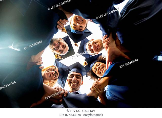 education, graduation, unity and people concept - group of happy international students in mortar boards and bachelor gowns standing in circle and holding hands