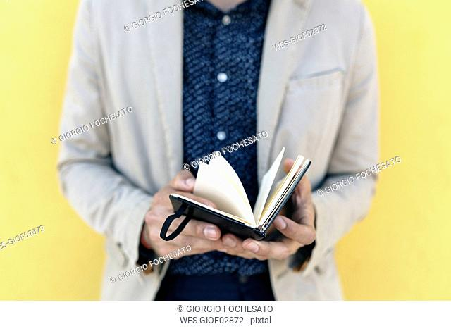 Man's hands holding note book, close-up