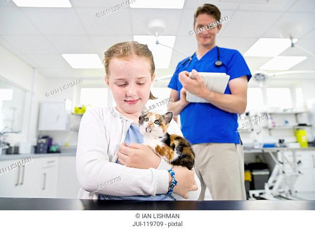 Vet with pet kitten cat on table in surgery with child owner