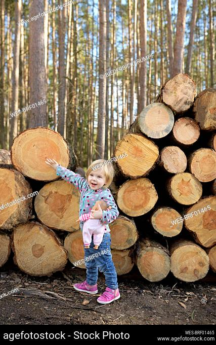 Portrait of happy little girl with doll standing in front of stack of wood in the forest