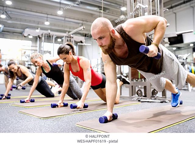 Group of athletes exercising with dumbbells in gym