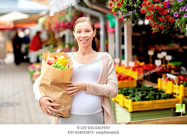 sale, shopping, pregnancy and people concept - happy pregnant woman with paper bag full of food at street market
