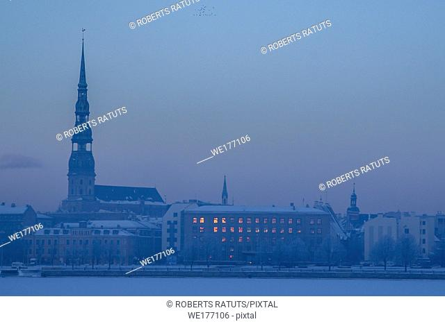 Riga view in winter; Riga, capital city of Latvia in winter time. View of St Peter's Church in winter. View of Old Riga with frozen river Daugava in the...