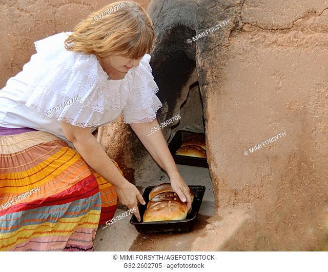 Baking bread in adobe horno, New Mexico, USA