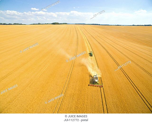 Aerial view of combine harvester in sunny golden barley field