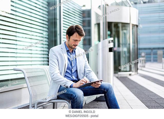 Businessman sitting on a bench, using digital tablet