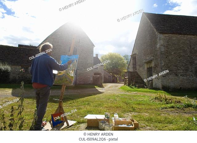 Man oil painting at easel outside farm buildings