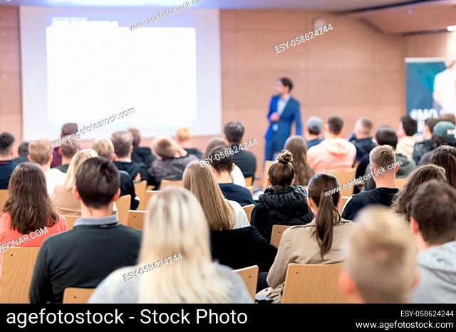 Speaker giving a talk in conference hall at business event. Audience at the conference hall. Business and Entrepreneurship concept