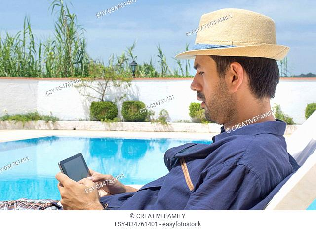 Man on the phone at the pool while on the vacation