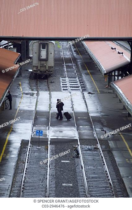 Wheeling their luggage, arriving passengers cross railroad station tracks in Portland, OR