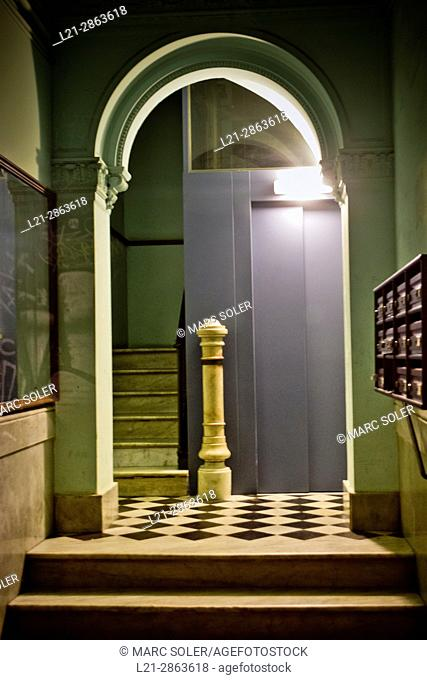 Entrance of a residential house at night. Interior with light, corridor, stairs and elevator. Barcelona, Catalonia, Spain