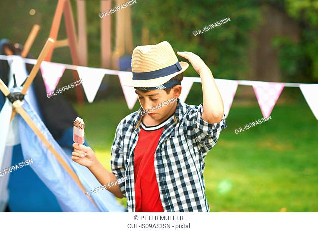 Boy eating ice lolly whilst adjusting trilby hat in garden