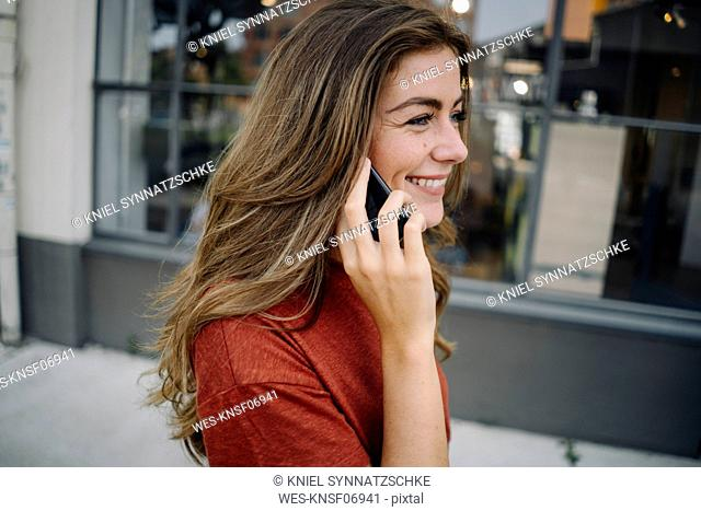 Portrait of smiling young brunette woman using smartphone