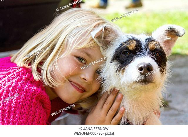Portrait of smiling litte blond girl and her Jack Russel Terrier