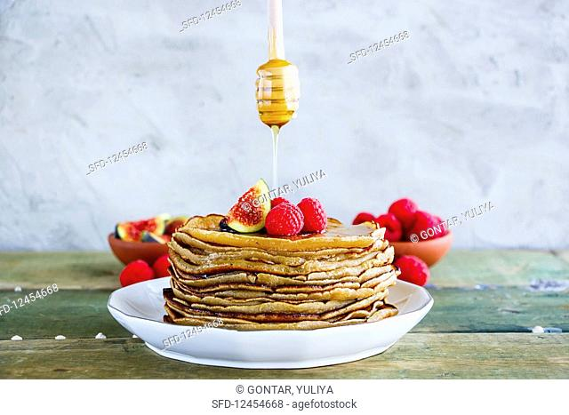 Sweet breakfast of homemade pancake tower with fresh figs and raspberries on white plate, and flowing honey from wooden honey dipper