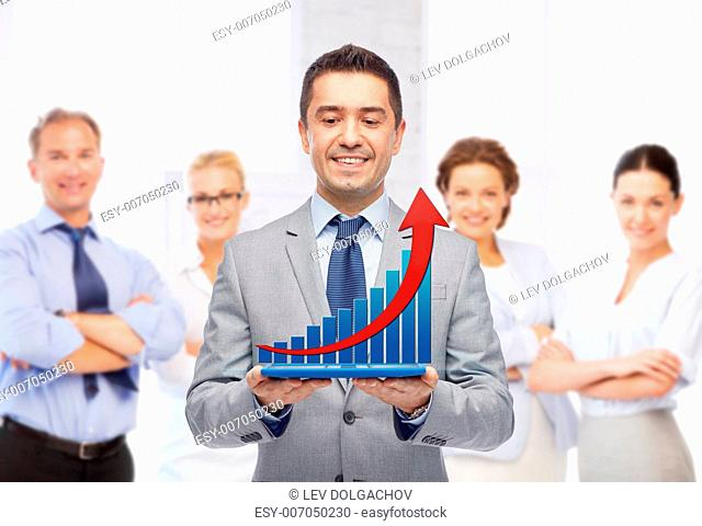 business, people, success and technology concept - happy smiling businessman in suit holding tablet pc computer with virtual graph over group of people and...