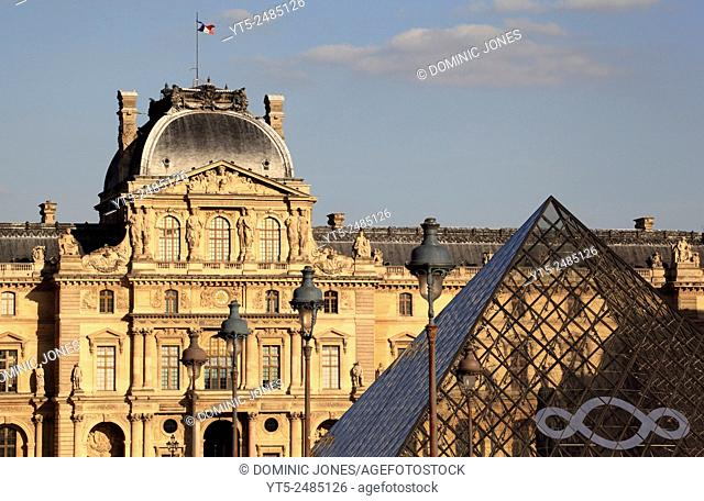 The Louvre and the Glass Pyramid catch the late summer light , Paris, France, Europe