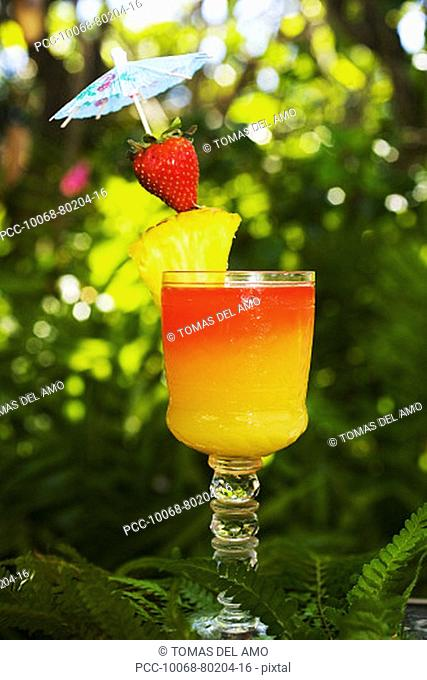 A tequila sunrise garnished with fruit in an outdoor setting