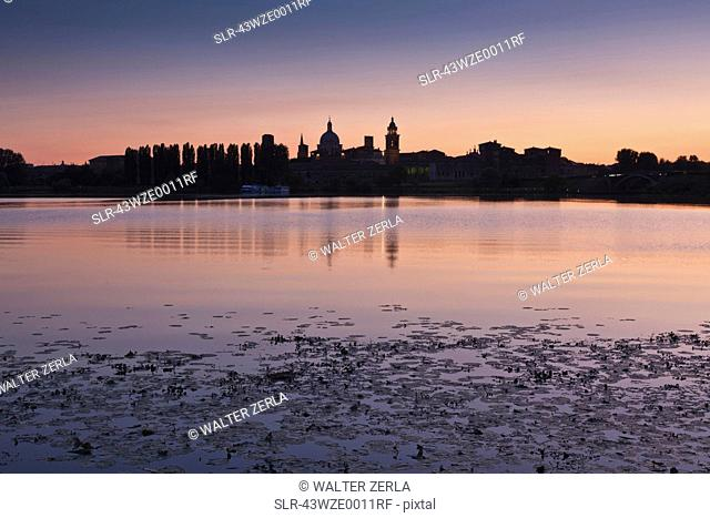 City skyline reflected in lake at sunset