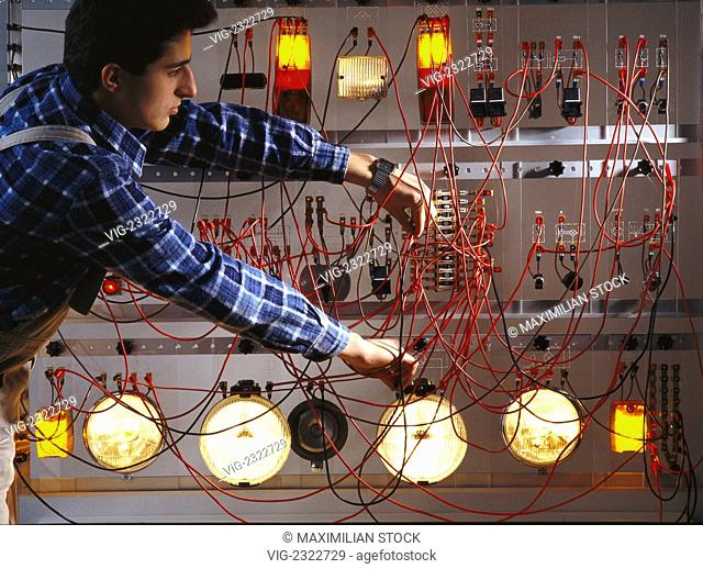 Motor car electronic engineers training. Trainee wiring an electrical and electronic test set-up - 01/01/2010