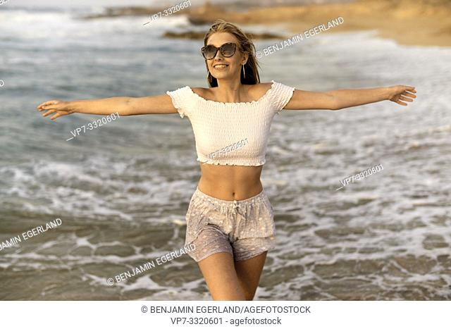 young happy teenage woman with open arms at beach, wet clothes, holiday, in Crete, Greece