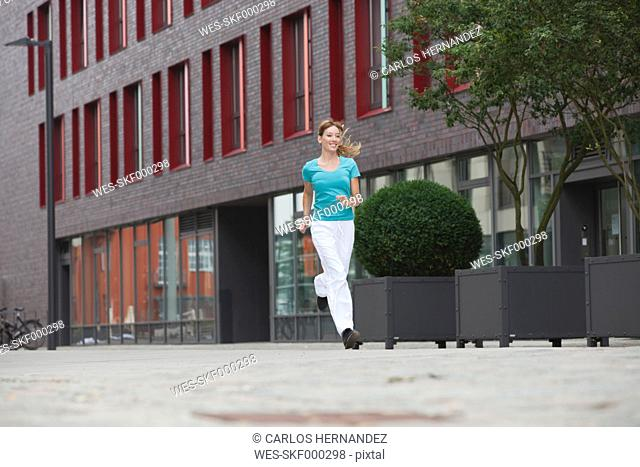 Germany, Cologne, Young woman jogging, smiling