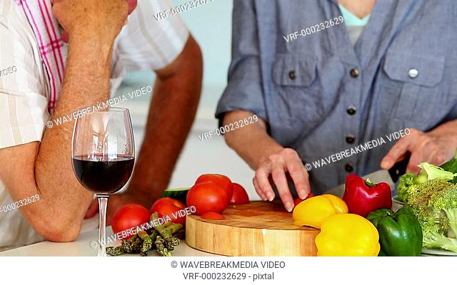 Senior couple preparing a healthy meal while drinking red wine at home in the kitchen