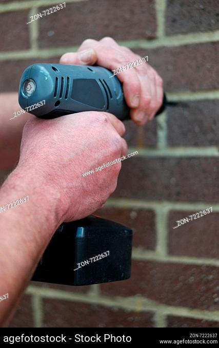 Man using a battery operated hand drill on a brick wall in a construction, renovations or DIY concept