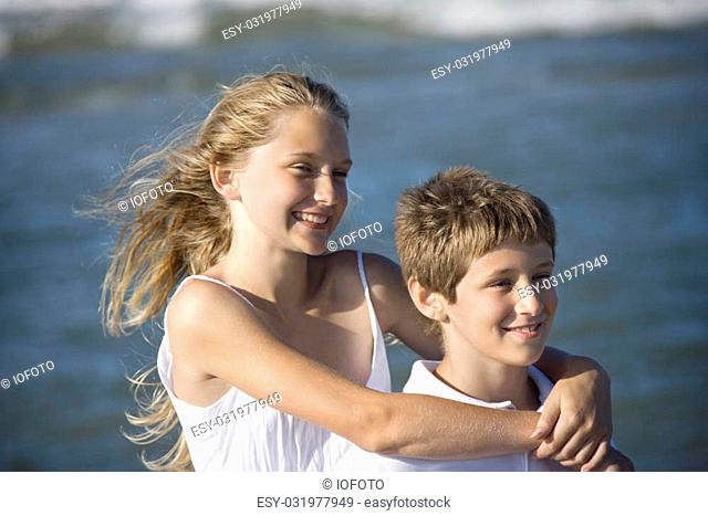 Caucasian pre-teen girl with arms around pre-teen boy on beach