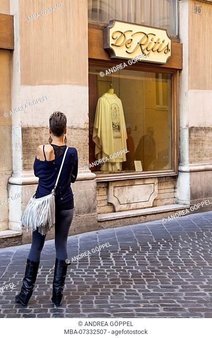 Italy, Rome, De Ritis, Via dei Cestari, woman in front of shop window, display of liturgical vestment