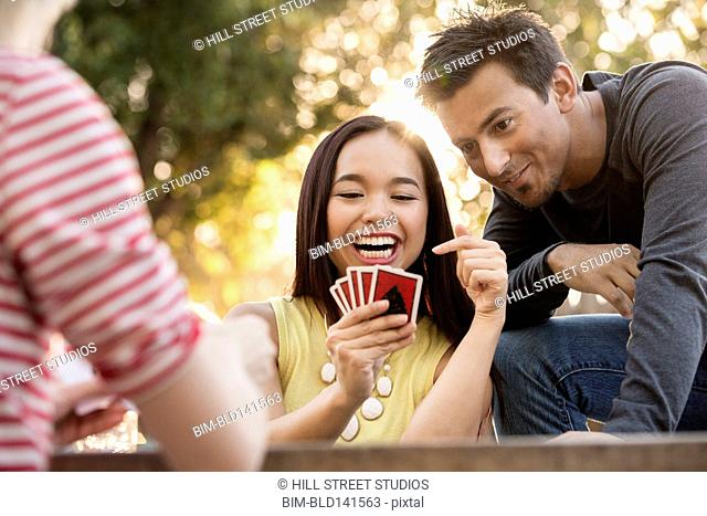 Friends playing card game in backyard