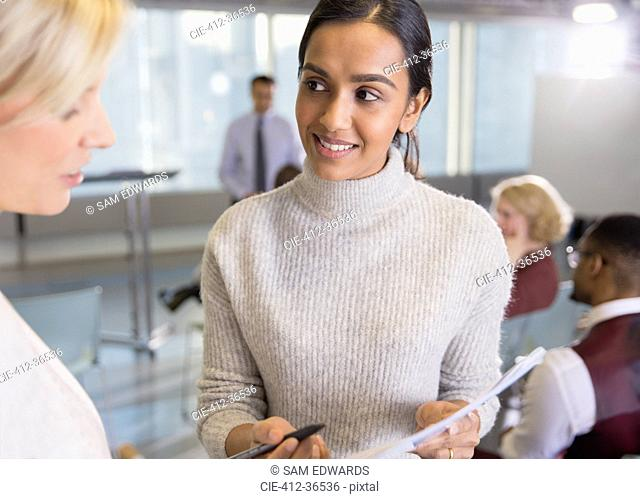 Businesswomen discussing paperwork in conference room meeting