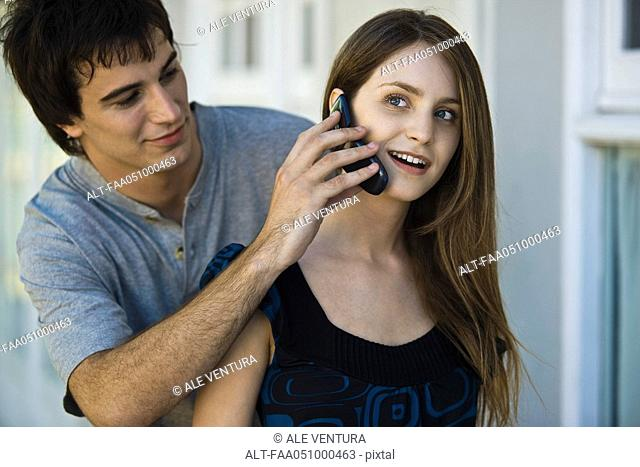 Young man holding cell phone to girlfriend's ear